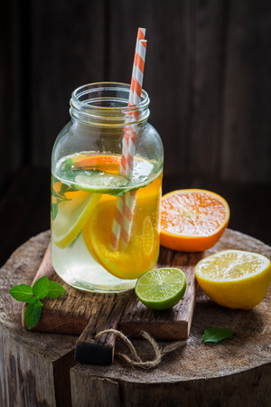 Water with citrus fruits and mint leaves on old stump Stock fotó