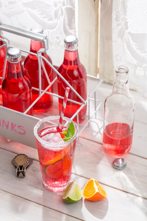 Red summer drink in bottle with mint leaf