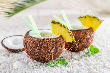 Tasty and fresh pinacolada in coconut on white pebbles