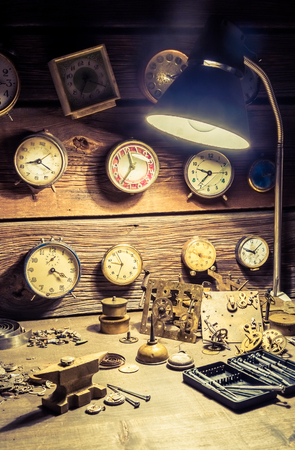 Old watchmakers workshop full of clocks and tools Stock Photo