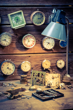 Watchmakers workshop with clocks, spare parts and tools