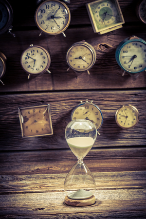 Hourglass as the old way of timing on clocks backgrounds Banco de Imagens