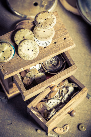 Wooden box with spare parts in watchmakers workshop