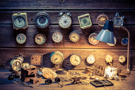 Watchmakers workshop with many clocks, tools and spare parts