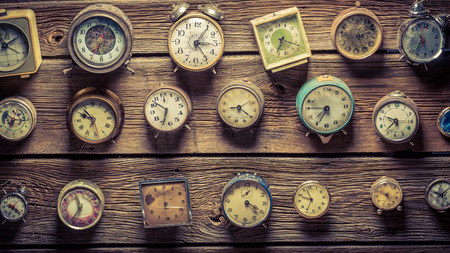 Mix of aged clocks on the wooden wall Stock Photo