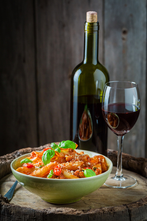 Delicious penne bolognese served with red wine