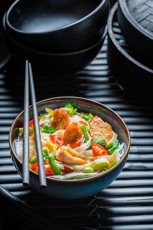 Closeup of noodle in dark bowl on black rock