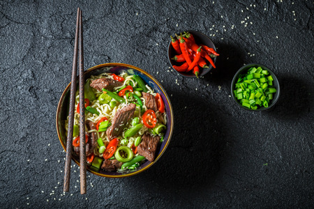 Enjoy your asian noodle with beef on black rock Фото со стока