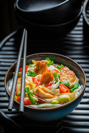 Hot noodle with vegetables and chicken on black table