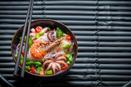 Enjoy your seafood noodle in dark bowl on black table
