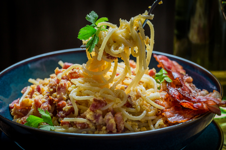 Closeup of tasty spaghetti Carborana with becon, parsley and eggs