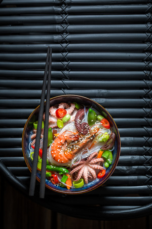 Tasty seafood noodle with prawn and octopus on black table Imagens
