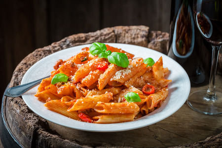 Tasty penne bolognese with parmesan and red wine