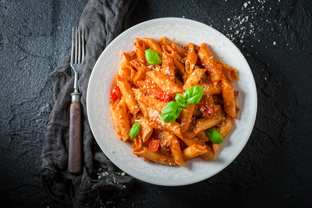 Tasty penne bolognese with parmesan and basil