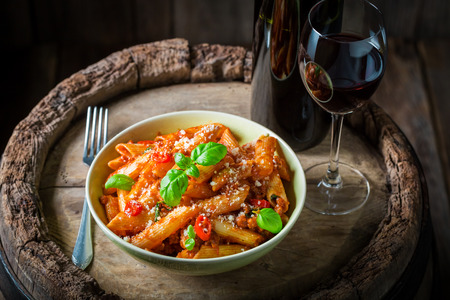 Homemade penne bolognese served with red wine