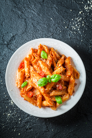 Delicious penne bolognese with parmesan and basil Фото со стока