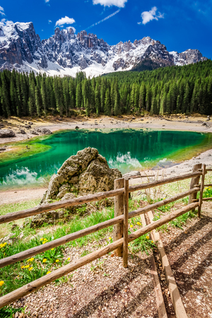 Big rock and green mountain Carezza lake in Dolomites, Italy Stock Photo