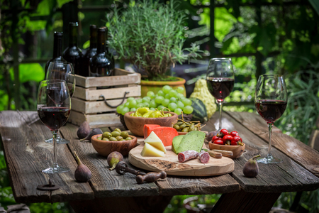 Garden table with snacks, wine and fruits in the evening Фото со стока