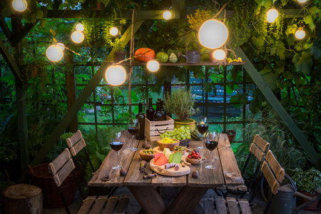 Garden table with appetizers and wine in summer evening