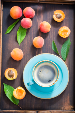Top view of coffee and plums on wooden tray