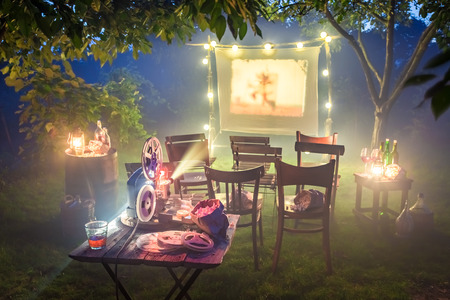 Small cinema with retro projector in summer garden
