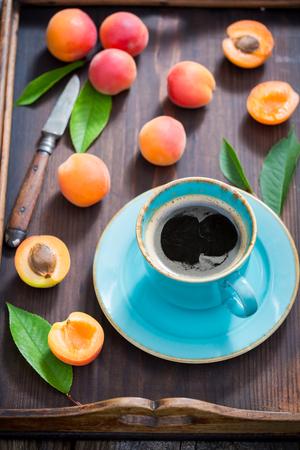 Plums and fresh coffee in summer garden Banco de Imagens