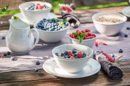 Closeup of breakfast with raspberries and blueberries in sunny day Stock Photo