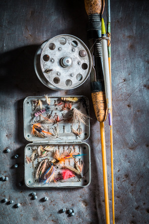 Fishing tackle with flies, floats and rods on metal table Фото со стока