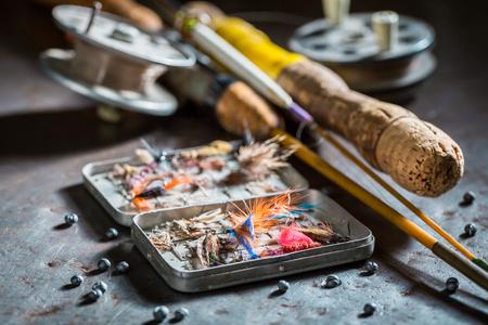 Matériel de pêche avec des mouches et des cannes à pêche sur table en métal Banque d'images