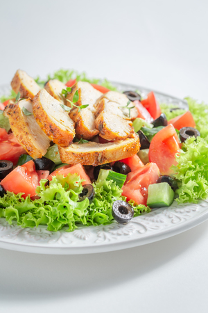 Delicious Caesar salad with olives, tomatoes and lettuce Фото со стока