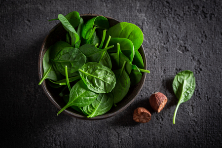 Fresh green spinach on gray old stone