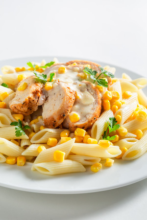 Yummy pasta with chicken, corn and bechamel sauce Фото со стока