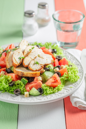 Delicious Caesar salad with tomatoes, cucumber and chicken
