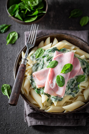 Hot pasta with spinach, ham and bechamel sauce Фото со стока