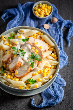 Tasty pasta with chicken, corn and bechamel sauce Фото со стока