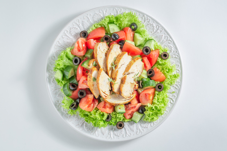 Fresh Caesar salad with chicken, olives and tomatoes Фото со стока
