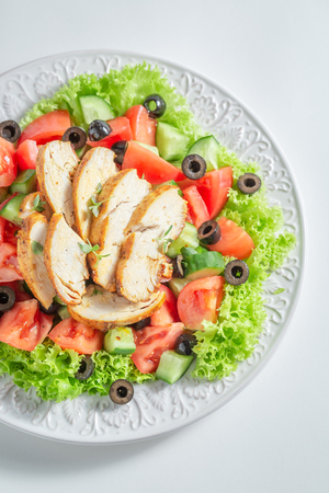 Tasty Caesar salad with chicken, olives and tomatoes