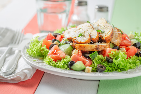 Healthy Caesar salad with olives, tomatoes and lettuce