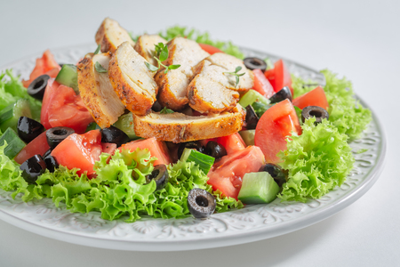 Fresh Caesar salad with tomatoes, cucumber and chicken