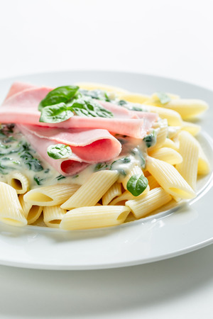 Tasty penne with spinach, ham and bechamel sauce
