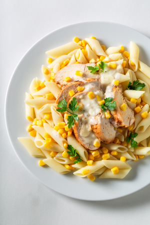 Tasty penne with bechamel sauce, chicken and corn Фото со стока