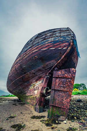 Abandoned old shipwreck on shore in Fort William, Scotland
