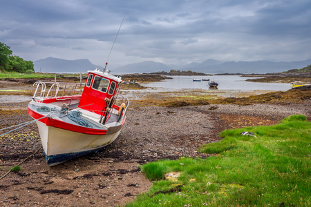 Red boat on the coast at low tide, Scotland