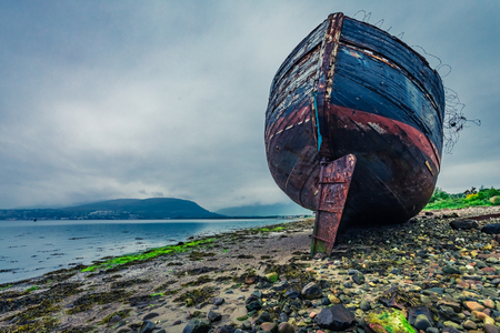 Abandoned ship wreck in Fort William in cloudy day, Scotland