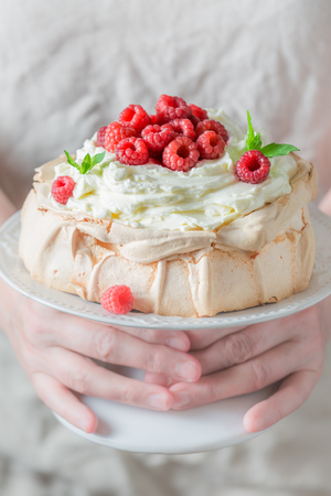 Pavlova dessert made of mascarpone and berries in woman hands