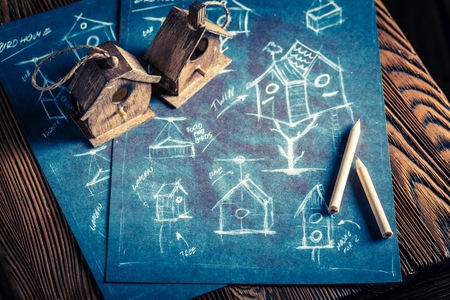 Closeup of project of small bird house in wooden workshop, drawing on blackboard