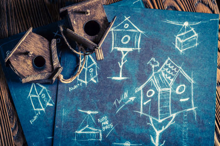 Homemade small bird feeder and blue construction plan drawing on blackboard Stockfoto