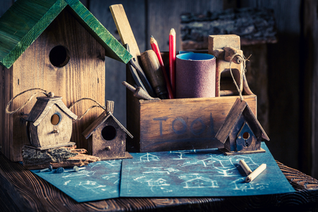 Homemade small bird feeder and blue plan to build it Stock Photo