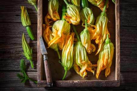 Fresh and healthy zucchini flower in old wooden box