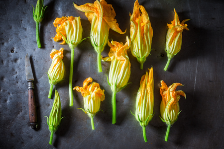 Ingredients for crispy roasted zucchini flower on metal table